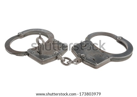 Handcuffs with a key within on white background - stock photo