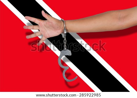 handcuffs with hand on Trinidad and Tobagoh flag