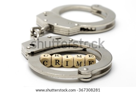 Handcuffs with word crime on wooden cubes - stock photo