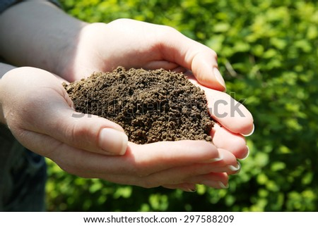 Handful of black soil over green grass background