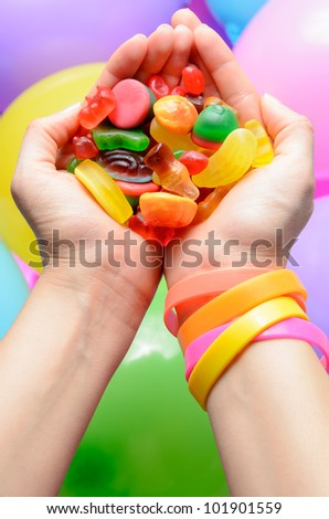 Handful of colorful jelly candies over balloons in a party concept. - stock photo
