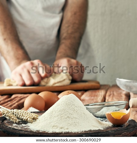handful of flour with an egg in a bakery. Against the background of men's hands knead the dough. concept, ingredients for cooking flour products or dough. Flour, egg, batter. Copy space. Close up - stock photo