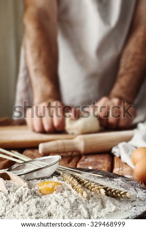 Handful of flour with egg yolks in a bakery. Against the background of men's hands knead the dough. Ingredients for cooking flour products. Copy space. Free space for text - stock photo