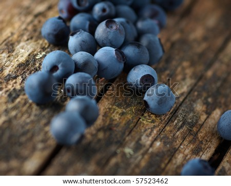 Handful of fresh blueberries on wooden surface, closeup - stock photo
