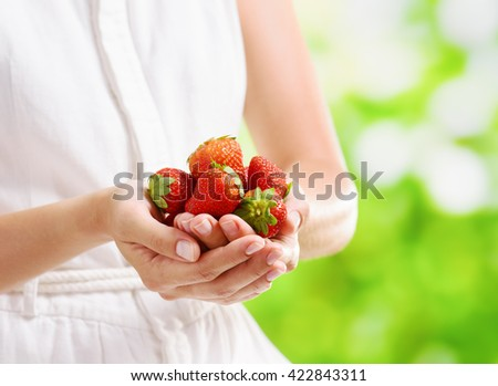 Handful of fresh ripe red juicy strawberries in hands of young woman in white dress on nature background. Healthy eco sweet food rich in vitamins. Popular product of organic farming.