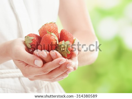 Handful of ripe red juicy strawberries in hands of young woman in white dress on nature background. Healthy eco sweet food rich in vitamins. Popular product of organic farming. - stock photo