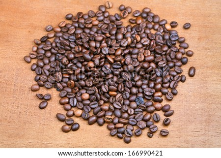 handful of roasted coffee beans on wood plank close up