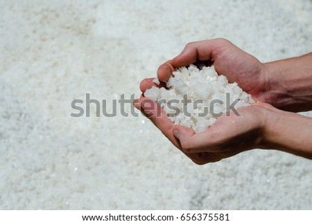 Handful of sea salt on salt background.