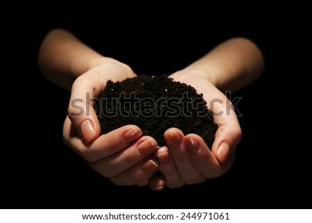 Handful of soil on dark background - stock photo