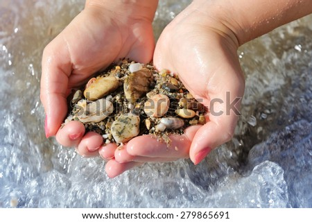 Handful of stones in hands, against sea - stock photo