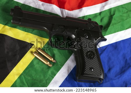 Handgun and brass bullets on South African flag - stock photo