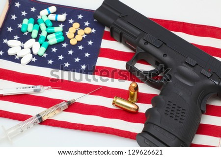 Handgun atop US flag with pharmaceuticals & two loose cartridges arrayed - stock photo