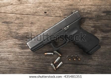 handgun bullets on wood table - stock photo