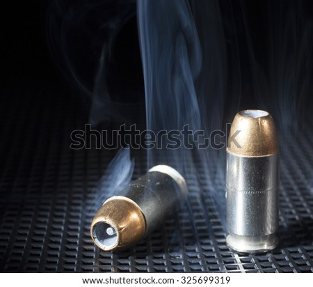 Handgun cartridges with hollow points and smoke - stock photo