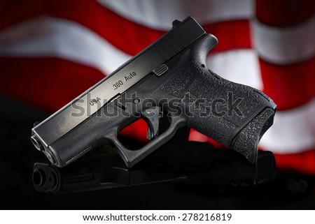 handgun on black with flag - stock photo