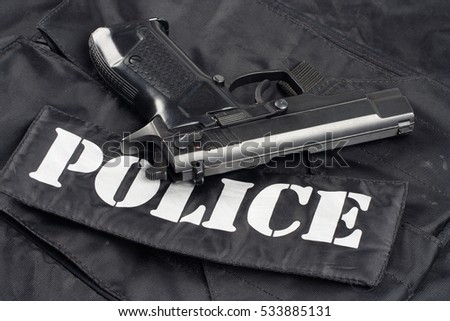 handgun on police black uniform background