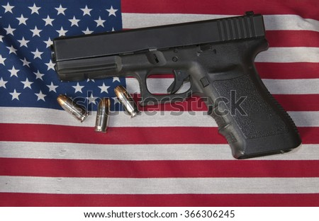Handgun over US flag with bullets
