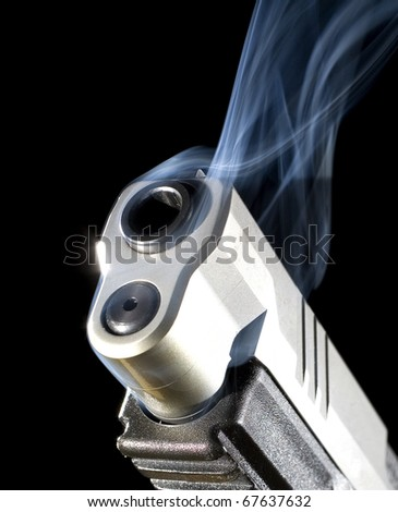 Handgun that has just been fired and belching out smoke - stock photo