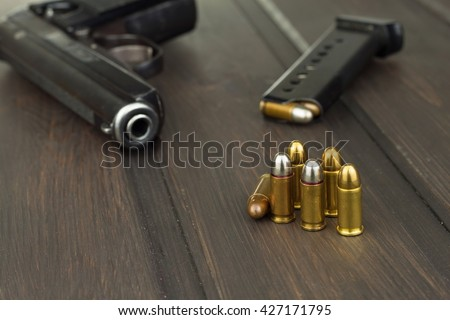 Handgun with ammunition on a dark wooden table. Sales of weapons and ammunition. Advertising on ammunition. New gun and ammunition. Grocery ammunition. The supply of ammunition for the defense. - stock photo