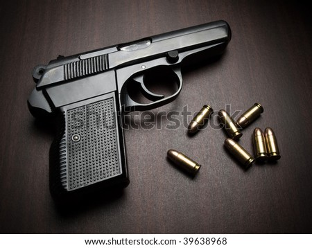 handgun with bullets on the wooden surface, closeup with vignette, useful for various security,protection or criminal topics - stock photo