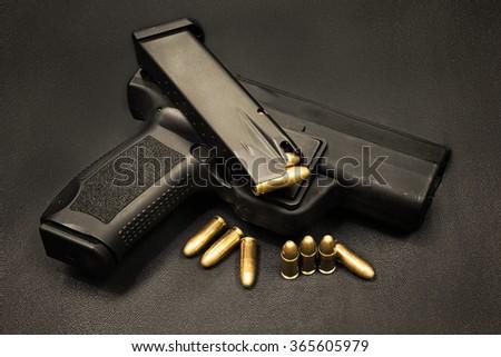 handgun with cartridge on the black background - stock photo