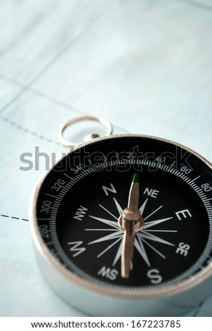 Handheld compass lying on a map showing the needle and cardinal points of north, south, east and west to aid in magnetic navigation to plot a route or direction to a specific destination - stock photo
