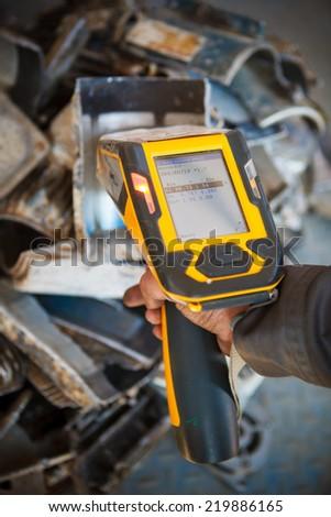 handheld XRF analyzer spectrometer for scrap metal in action - stock photo