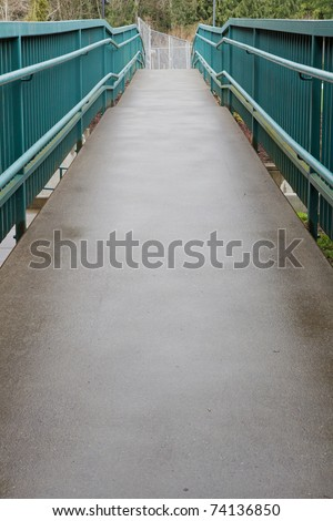 Handicap accessible green railing ramp going up - stock photo