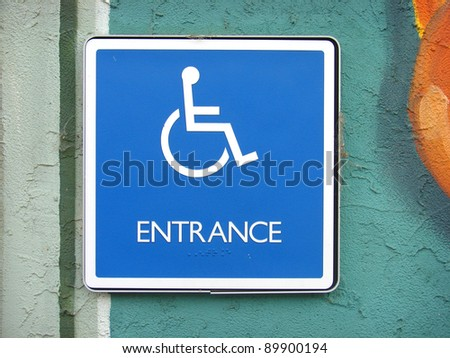 handicap entrance sign on painted stucco wall - stock photo