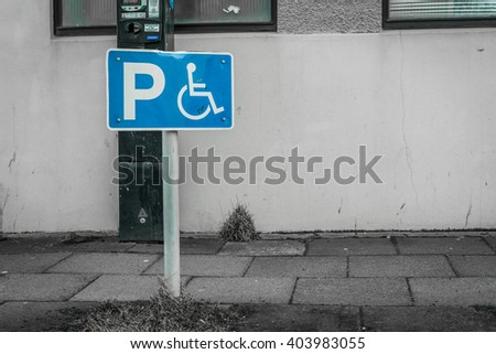 Handicap parking sign on a street in front of a building - stock photo