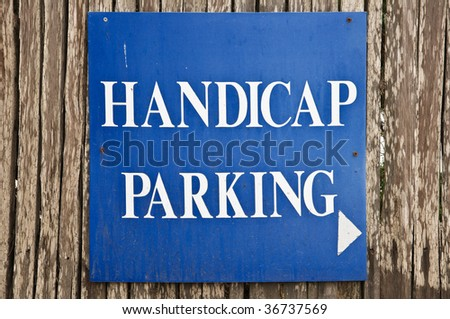 Handicap parking sign on wooden fence - stock photo