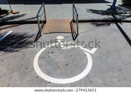 handicap signs with wheelchair at entrance of concrete ramp - stock photo