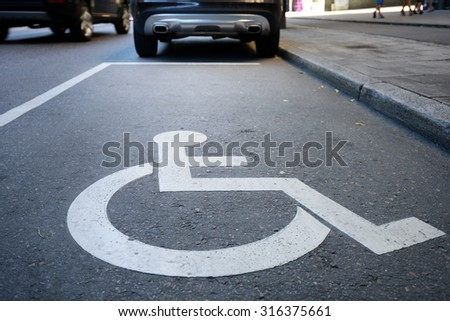 Handicap symbol on road, traffic and pedestrians in background - stock photo