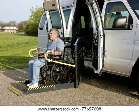 handicap van with a man in a wheelchair on a lift - stock photo