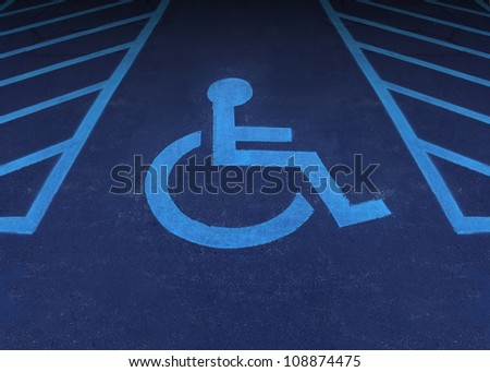 Handicapped and disabled symbol as a parking space with a wheelchair painted on asphalt as a health care and medical icon of reserved space for accessibility of the physically challenged. - stock photo