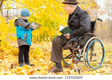 Handicapped elder man with one leg amputated sitting in a warm overcoat and hat in his wheelchair in a colourful autumn park watching his grandson play on his tablet computer - stock photo