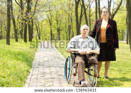 Handicapped elderly man with one leg amputated above the knee sitting in his wheelchair in a wooded park with his wife standing at his side - stock photo