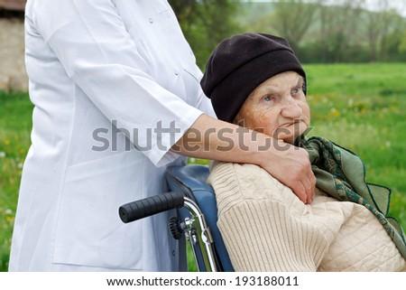 Handicapped elderly sitting in her wheelchair  - stock photo