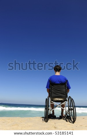 handicapped man in a wheelchair watching the sea - stock photo