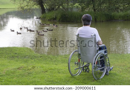handicapped man on a wheelchair alone in a park,in front of a lake - stock photo
