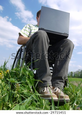 Handicapped man on wheelchair using laptop outdoors - stock photo