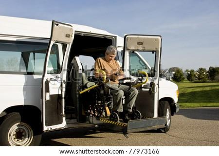 handicapped man operating a wheelchair lift van - stock photo