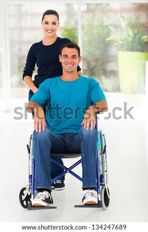 handicapped man sitting on wheelchair with caring wife at home - stock photo