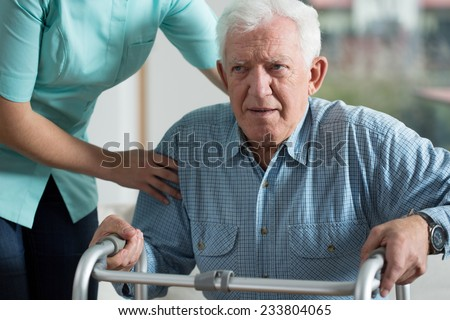 Handicapped man using walker - rehabilitation at home - stock photo