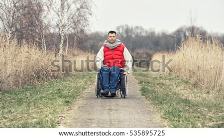 handicapped man with wheelchair outside in nature