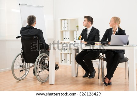 Handicapped Mature Businessman Explaining To His Colleagues In Office - stock photo