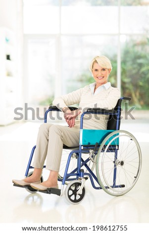 handicapped middle aged woman sitting in wheelchair - stock photo