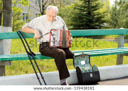Handicapped senior man sitting on a park bench in the sunshine with an accordion - stock photo