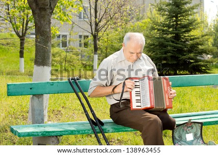Handicapped senior man with one leg amputated above the knee sitting on a park bench playing the accordion - stock photo