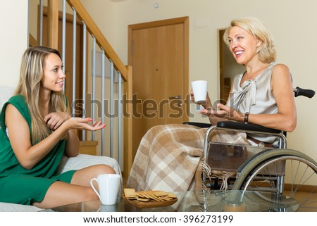Handicapped smiling woman talking with female guest at the table. Focus on young - stock photo